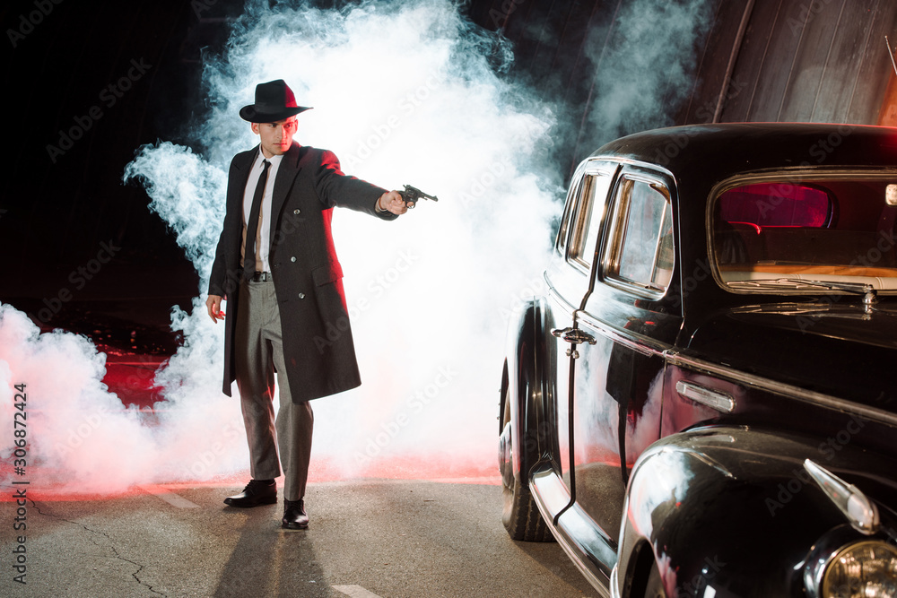 Fototapeta stylish gangster in hat holding gun near retro car and smoke