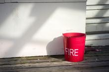 A Red Fire Bucket On Wooden De...