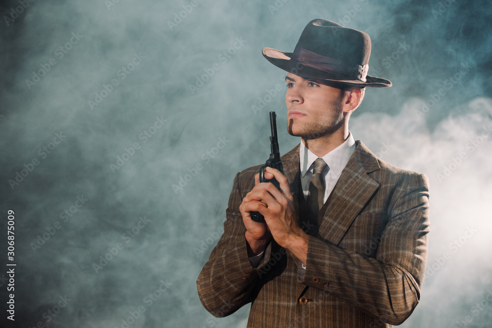 Fototapeta handsome gangster in hat holding gun on black with smoke