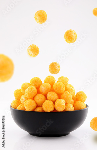 Valokuva puffed ball cheese corn chips in black bowl on white background