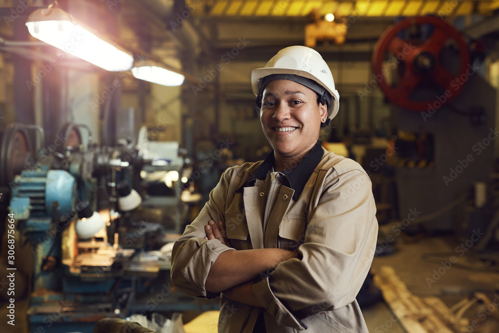 Fototapeta Waist up portrait of mixed-race female worker posing confidently while standing with arms crossed in factory workshop
