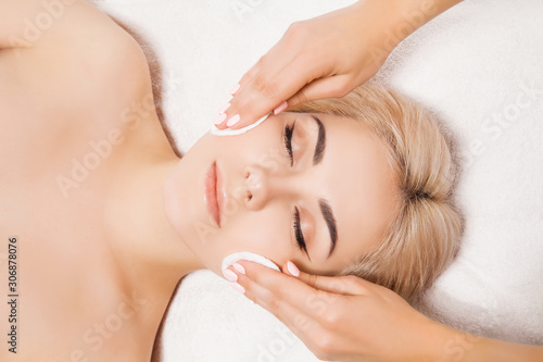 Doctor beautician cleanses face skin with sponge in beauty salon Canvas Print