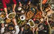 Traditional Turkish celebration dinner. Flat-lay of people feasting at table full of Turkish salads, cooked vegetables, meze starters, pastries and raki drink, top view. Middle Eastern cuisine