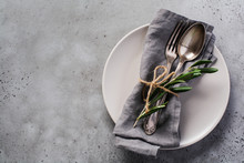 Rustic Vintage Set Of Cutlery. Plate With Grey Linen Napkin, Fork And Spoon, Olive Tree Branch Over Rustic Concrete Gray Old Background. Fall Holiday Table Decoration Setting. Top View, Copy Space.