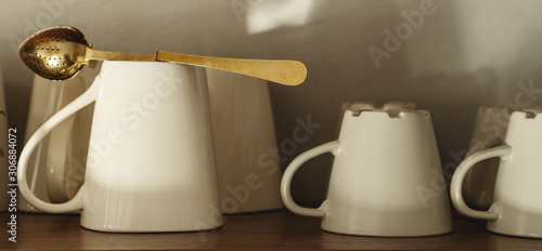 Fotografie, Obraz  Set of Cups and standard strainer Tea Infuser Mesh Spoon Stainless Steel on the shelf with copy space, close view