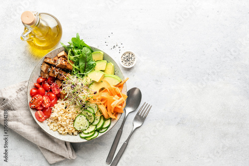 Fototapeta Vegetarian Vegan salad bowl or buddha bowl with grains, tofu, avocado, vegetables and greens. Balanced meal on grey concrete background. Top view, copy space obraz