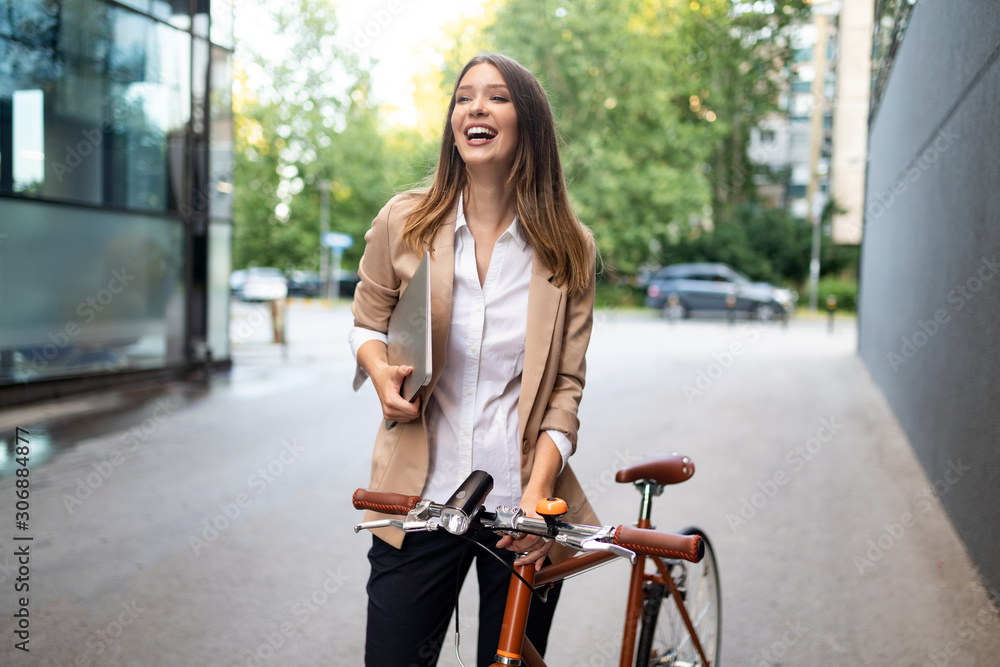 Fototapeta Business woman with bicycle to work on urban street in city. Transport and healthy lifestyle concept