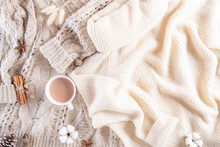 Autumn Or Winter Composition. Coffee Cup, Cinnamon Sticks, Anise Stars, Beige Sweater On Cream Color Knitted Blanket Background. Flat Lay Top View Copy Space.