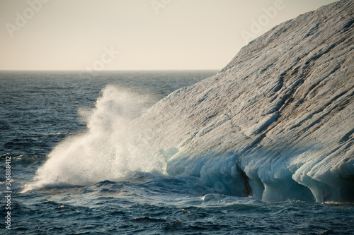 Sea spray is formed as sea water crashes against a drifting iceberg in Arctic waters Canvas Print