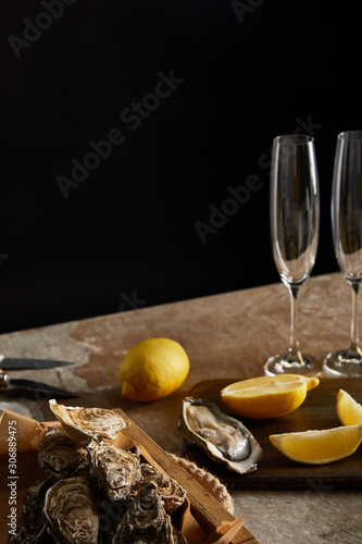 Photo selective focus of oysters in shells near lemons on wooden cutting board and cha