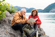 A Senior Pensioner Couple Hiking By Lake In Nature, Using Map.