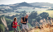 canvas print picture - Senior tourist couple travellers hiking in nature, walking.