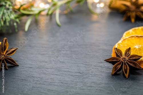 Photo Winter holiday still life concept on dark slate board with dried oranges, anise