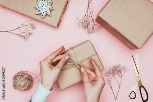 cropped view of girl packing christmas presents with craft paper, twine and flow Fototapet