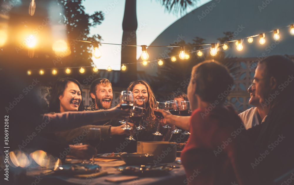 Fototapeta Happy family dining and tasting red wine glasses in barbecue dinner party - People with different ages and ethnicity having fun together - Youth and elderly parents and food weekend activities concept