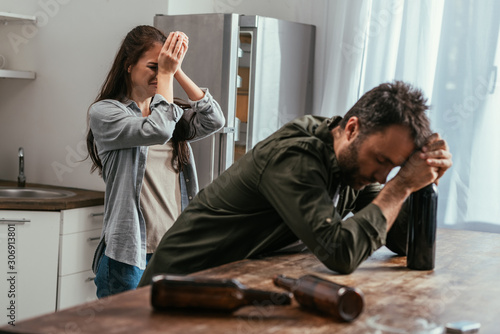 Photo Selective focus of crying woman with alcohol addicted husband on kitchen