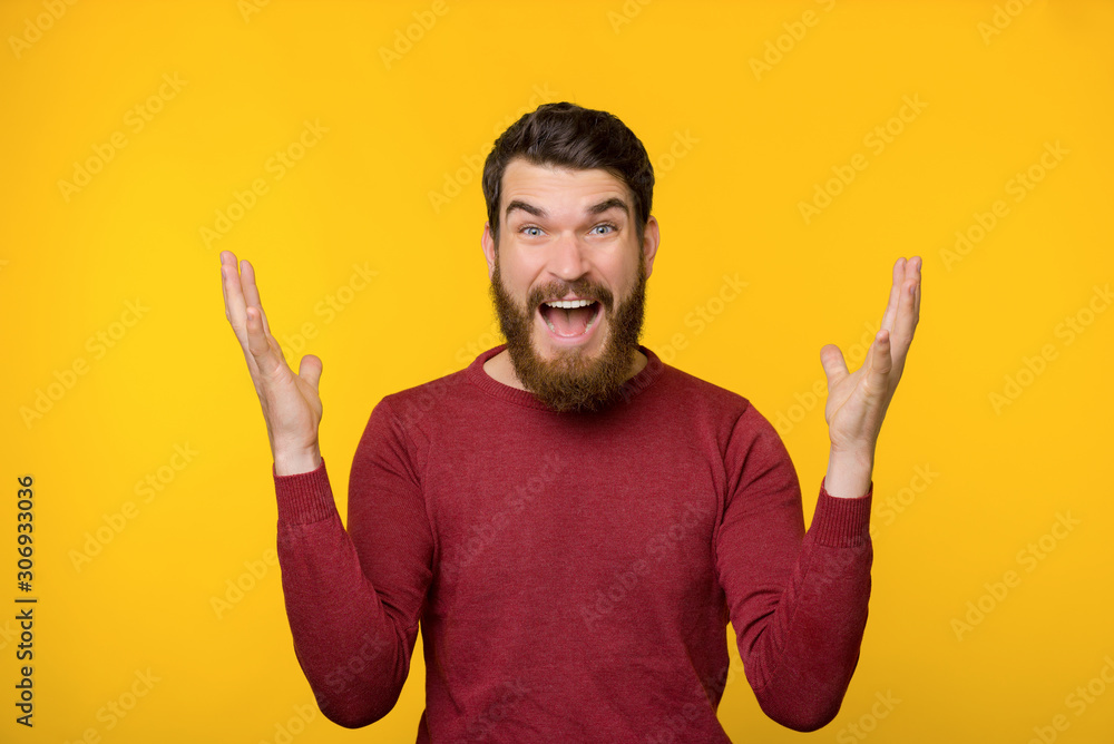 Fototapeta Bearded young man being surprised near yellow wall.