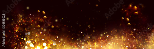 Fotografie, Obraz Golden Christmas and New Year glittering stars swirl on black bokeh background, backdrop with sparkling golden stars, holiday garland, magic glowing dust, lights