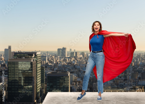 Cuadros en Lienzo  women's power and people concept - happy woman in red superhero cape over tokyo