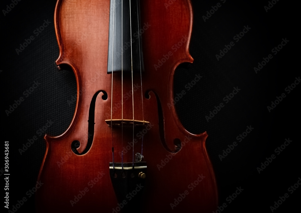 The wooden violin put on black canvas background,show front side of string instrument,vintage and art tone,blurry light around