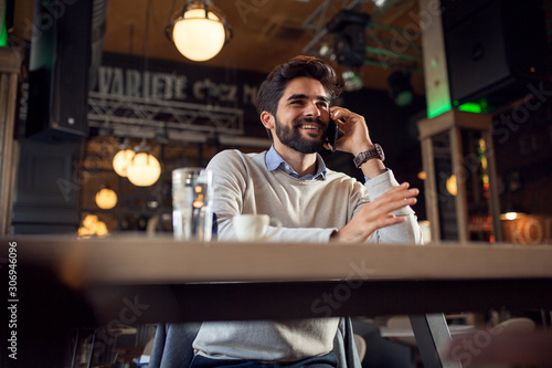 Handsome beard man talking on phone while sitting in cafe bar Canvas Print
