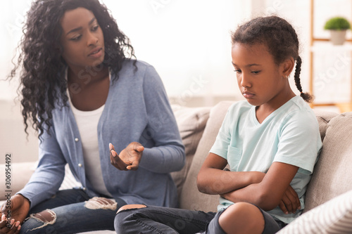 Disappointed black mother looking at her little daughter with reproach Tablou Canvas