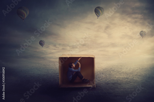 Surreal scene as a trapped guy want to get out of a cardboard package, needs to think outside the box Tablou Canvas