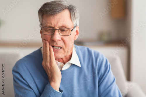 Stampa su Tela Elderly Man Having Toothache Sitting On Sofa At Home