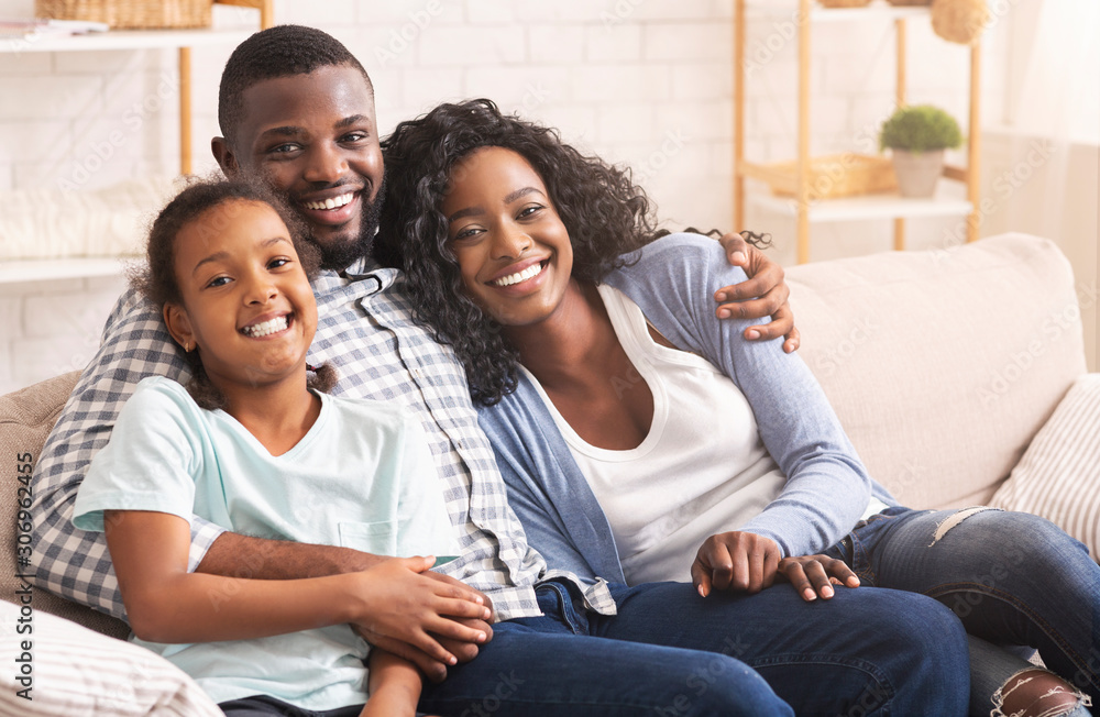 Fototapeta Loving afro family cuddling and smiling to camera at home