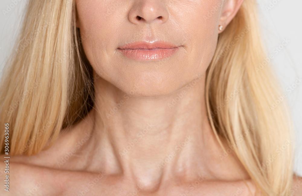 Fototapeta Beautiful mature woman with wrinkled neck, grey background