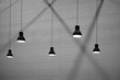 Leinwanddruck Bild - Side view and selective focus of 5 hanging lamps with light and shadow on surface of brick wall background in black and white style, interior architecture design concept