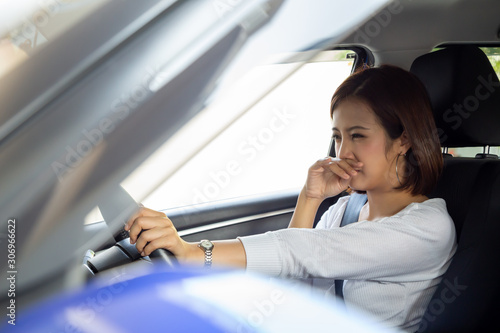 Valokuva  Young Asian woman hold her nose because of bad smell dirty in car