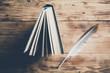 Leinwanddruck Bild - feather on book on the wooden table