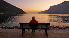 Lonely Old Man Sits On A Wooden Bench At Dusk Looking At The Lake And The Light On The Horizon.