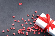 Red Heart Shaped Sprinkles With Gift Box On Black Background