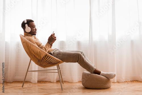 Fototapeta Relaxed Black Man In Headset Using Phone Listening Audiobook Indoor obraz na płótnie
