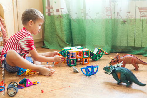 Child building a dinosaur from magnetic constructor on floor in children room nearby window