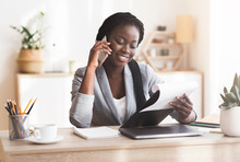 Black Female Manager Making Phone Call And Checking Reports In Office