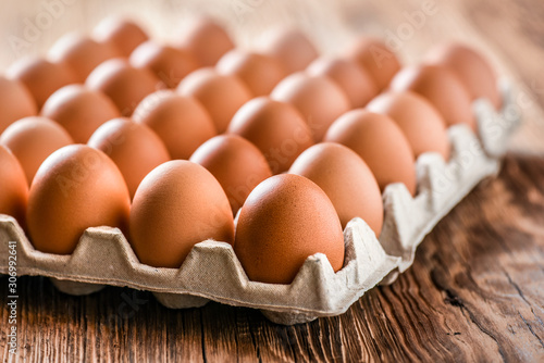 Brown Egg, Chicken eggs in caton on wooden table. Fototapet