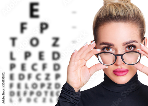 Photo Woman in glasses and eye chart. Ophthalmologist consultation.