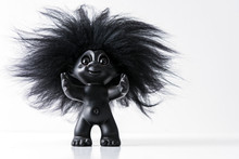 A Black Happy Toy Troll With Big Har And Arms Wide Open Isolated On White Studio Background With Copy Space For Text.