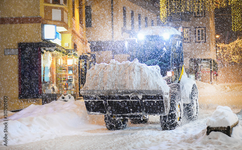 Obraz na plátně Highway maintenance heavy truck cleaning road during blizzard or snowstorm in evening, winter transport calamity removing in center of city