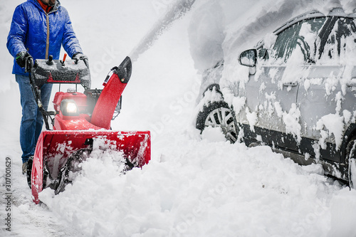 Man clearing or removing snow with a snowblower on a snowy road detail Canvas Print