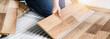 Leinwanddruck Bild - Worker hands installing timber laminate floor. Wooden floors house renovation with measure items.