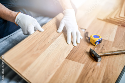 Man installing laminated wooden floor, Professional floor work in new house.