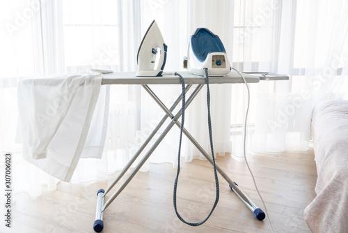 Fotografia Steam generator iron standing on ironing board near window with white shirt