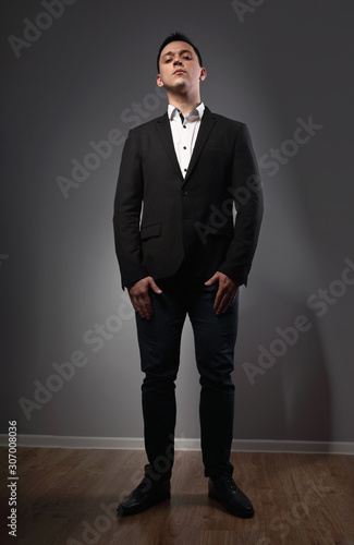 Photo Serious thinking man looking in black suit on grey studio background