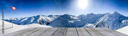 Fototapeta wooden shelf in front of snow mountain range obraz