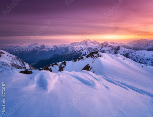 Colorful red sky with clouds and bright sunlight over the snow covered mountains at sunset in winter Canvas Print