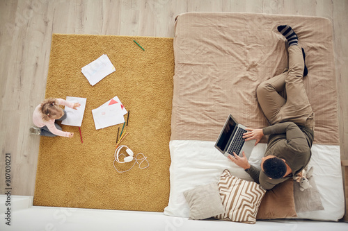Obraz Above view background of little girl playing on floor in cozy bedroom interior with father using laptop, copy space - fototapety do salonu